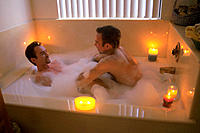 Gay men enjoy bubble bath together