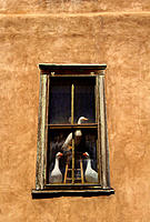 Trio of geese statues gazing from the window of an adobe building in Santa Fe. New Mexico. USA