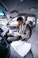 Businessman in car with cell phone and laptop computer