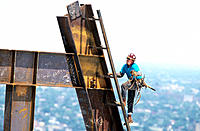 Iron worker climbs column at construction site