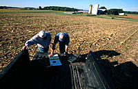 Farmers with laptop computer by planter. Ohio. USA