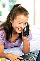 Teen girl on phone using laptop in bedroom