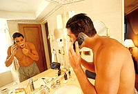 Latin man shaving while talking on cellular in a hotel bathroom