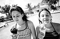 Two teenage girls enjoying eating ice cream together on hot day at the swimming pool