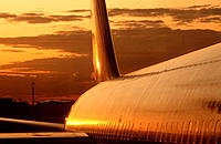 Fuselage of Boeing 767 aircraft reflecting sunset sky