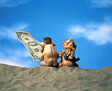 Two hog figurines sitting atop sand bank holding one hundred U.S. bill