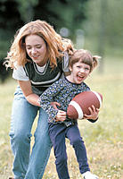 Mother and Daughter Playing With Football