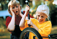 Girl taking hammer to bicycle wheel