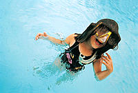 Girl emerging from water with hair cover face and goggles