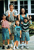 Young family outside home thumbs-up