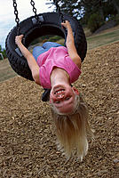 Little girl plays on tire swing
