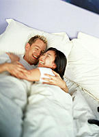 Man and woman laugh & embrace in bed