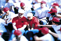 Alienated twosome wearing red shirts jeered by crowd wearing white shirts