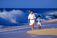 Father & son walk along shoreline, large blue waves breaking in bkgd C1099
