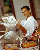 Handsome man sits reading newspaper, slight smile cosmopolitan D1133
