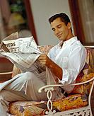 Handsome man sits reading newspaper, slight smile cosmopolitan D1133