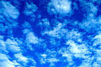 Puffs of small clouds, alto-cumulus scattered in blue sky
