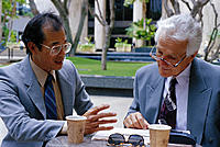 Senior caucasian businessman and Asian sit at outdoor table, talking over coffee
