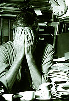 Stress. Office worker with his hands to his face.