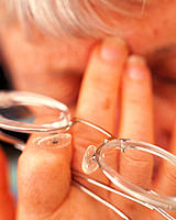 Headache. Elderly woman pressing her fingers against her forehead due to a headache or a migraine. She has taken off her glasses. Migraines result in ...