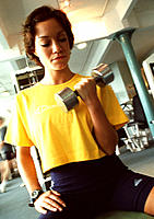 Workout. Woman using a dumb-bell to exercise her arm.