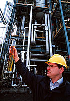 Biodiesel manufacture. Biofuel production plant worker holding a sample of biodiesel produced from rape seed  oil. Photographed at the Novaol plant, L...