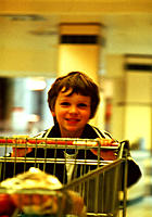Shopping. Smiling boy pushing a trolley around a supermarket.
