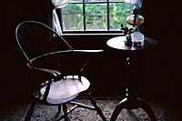 Room interior with empty wooden chairs by window, sunlight coming in, in Pioneer Village, Spring Mill state Park, Indiana, USA
