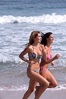 Side profile of two young women running on the beach