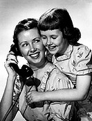 Mother holding a telephone with her daughter hugging her from behind