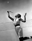Low angle view of a young woman playing badminton