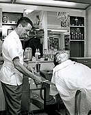 Side profile of a barber preparing a razor for shaving