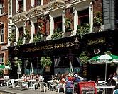 Group of people sitting at a sidewalk cafe, Sherlock Holmes Pub, London, England