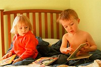 Two year old boy gestures to two year old girl on bed while reading childrens books