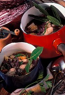 Red cabbage soup with sausages and bay leaf in pots