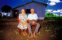 Couple of old farmers sitting in front of their ranch. Misiones province. Argentina