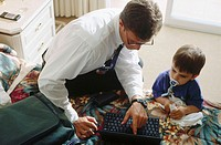 Father with son working with laptop computer