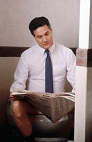 Businessman sitting on the toilet reading the paper