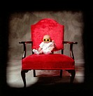 Three-month old boy sitting on red chair wearing neon yellow glasses