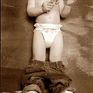 Two-year old boy with pants down wearing diapers