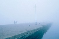 People walking along the pier in fog, Trieste, Italy