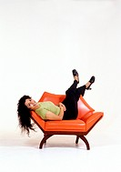 Ethnic Woman Reclines in Orange Chair
