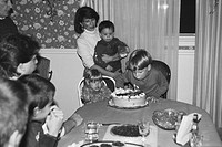 Boy Blowing out Candles on Birthday Cake at Party, Sepia'