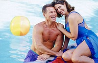 Middle aged couple in pool, woman sits on edge