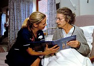 CREDIT: JOHN COLE/SCIENCE PHOTO LIBRARY  Hospital menu.  Nurse helping  an elderly  patient who is choosing food from a menu. Photographed at St Richa...