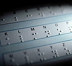 Braille alphabet. Part of a sheet written in braille with the corresponding characters typed above each braille letter. The braille writing and readin...