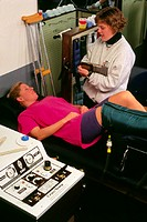 Cold treatment for sprained ankle. Woman lies on a bench with her raised foot inside a pressurised cold water jacket (Jobst cryo/temp machine) designe...