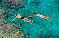 Couple snorkling in cristal clear waters of Curaçao.