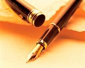 Photo of a fountain pen, desk, paper, pen.