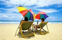 Couple sitting under umbrellas at Hikkaduwa beach. Sri Lanka